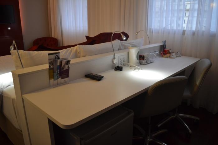 A mesa de trabalho fica junto à cama