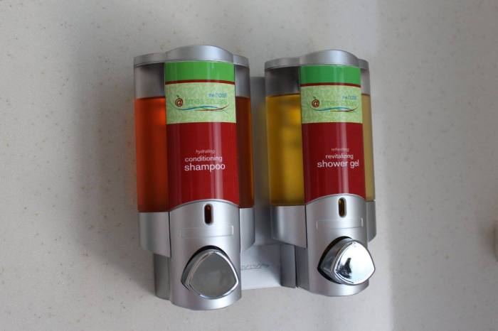Dispensers com xampu e sabonete próximo às ducha e banheira.